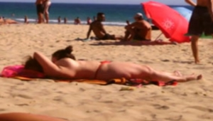 Coroa fazendo topless na praia exibindo peitos grandes